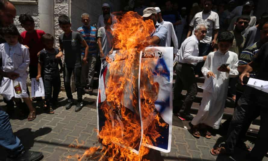 Palestinians burn a poster of Donald Trump