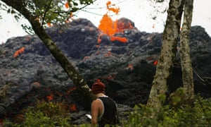 A lava fissure erupts as a resident stands nearby in Pahoa, Hawaii.