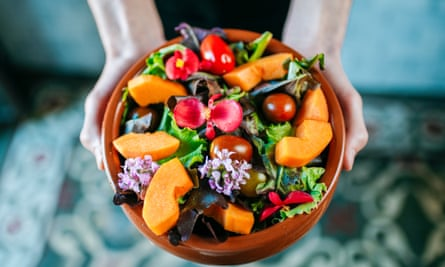 Bowl of salad garnished with edible flowers