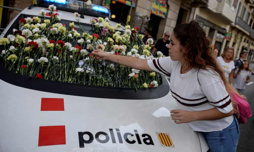 A woman puts a flower on a Catalan police car during a pro-independence referendum rally in Barcelona