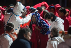 Women are helped to disembark from a migrant rescue vessel in Málaga, Spain