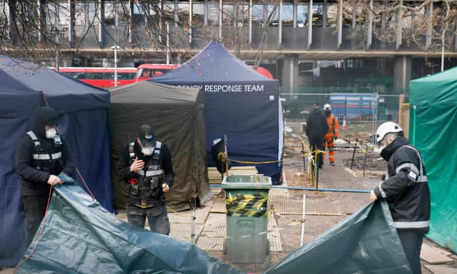 Bailiffs work with a tarpaulin near the entrance to tunnels dug and occupied by environmental activists protesting against the HS2 high speed rail line near Euston Station in London on Friday.