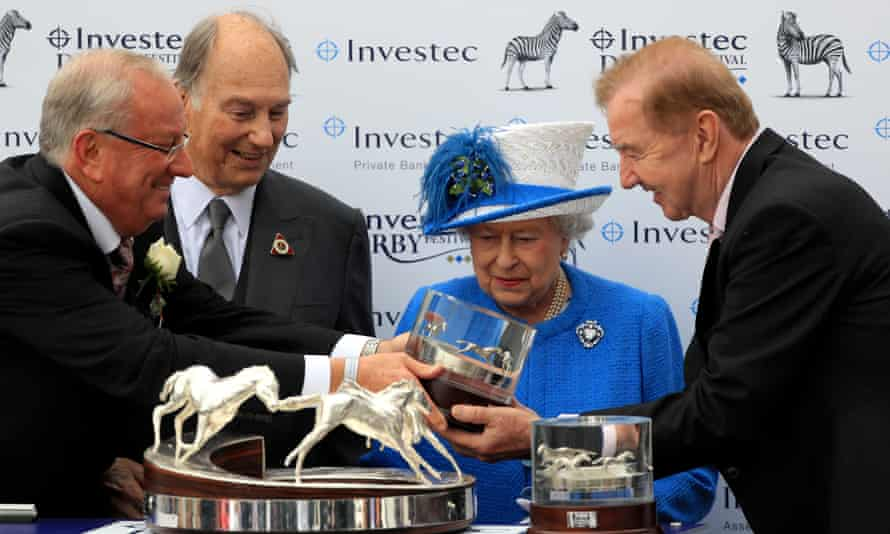 The Queen watches as the trophy is presented to Dermot Weld, right, after Harzand, owned by the Aga Khan, second left, won the Derby.