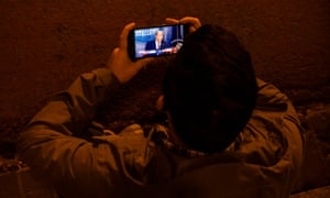 A man watches President Donald Trump speak from the White House on his phone at Black Lives Matter Plaza in Washington DC.