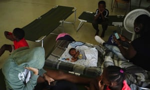 Anastacia Makey and her family sits on cots with other residents inside a church opened as a shelter, in Freeport on Grand Bahama.