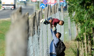 A family hop over the fence at the migration centre in Roszke, Hungary.