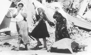 Palestinian women pass a victim of the massacres in the Palestinian refugee camp of Sabra, in West Beirut in 1982.