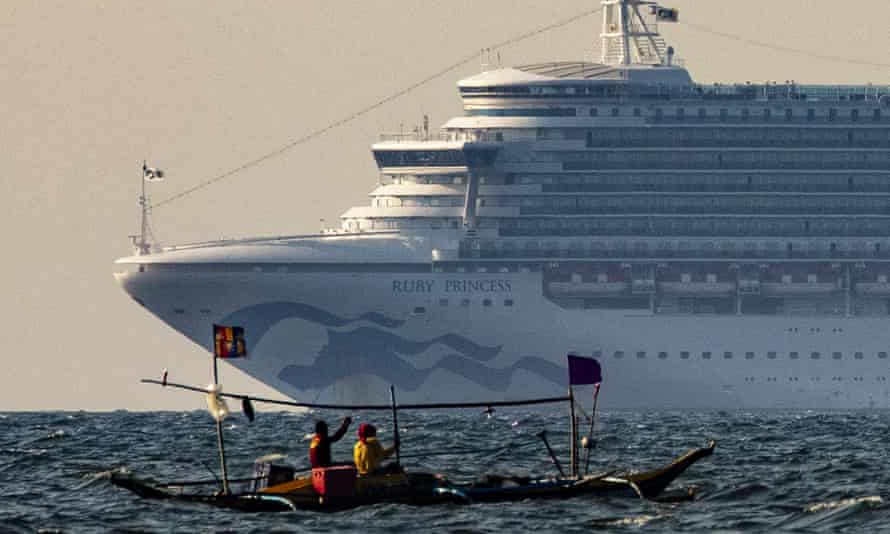 A small fishing boat passes by the Ruby Princess in the waters of Manila Bay, Philippines, 7 May 2020