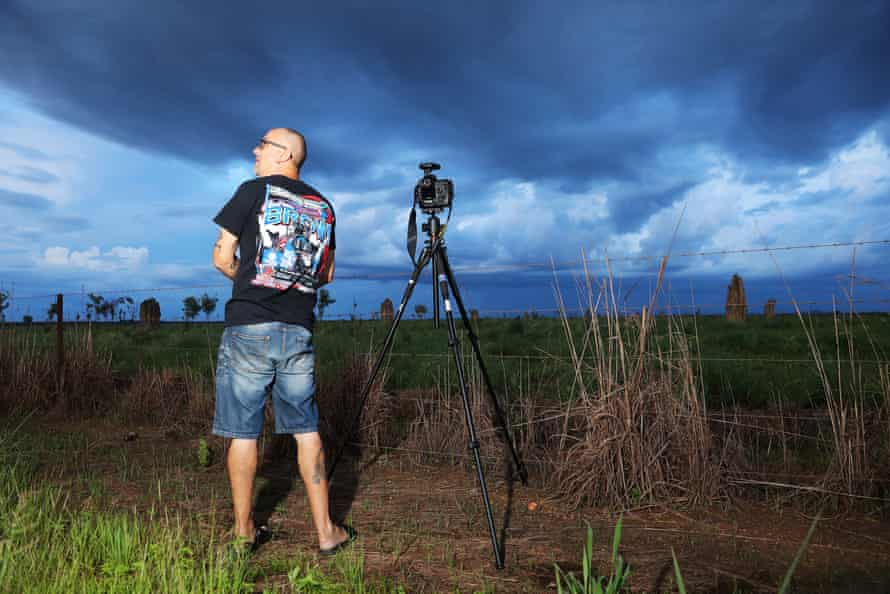 Mike O'Neill sets up his camera beside a dirt road overlooking a range of ant hills