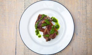 Lamb chops on a plate with crisped fat, slightly pink meat pink and bright green sauce dotted across