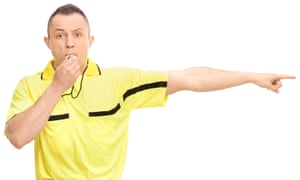 An angry football referee blowing a whistle and pointing with his hand