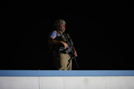 An armed civilian stands on a roof during protests over the shooting of Jacob Blake by a police officer in Kenosha, Wisconsin.