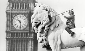 Illtyd Harrington with broom, sitting on Lion statue with St Stephen's tower ('Big Ben') in background