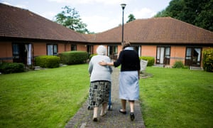 Older woman being helped to walk by carer