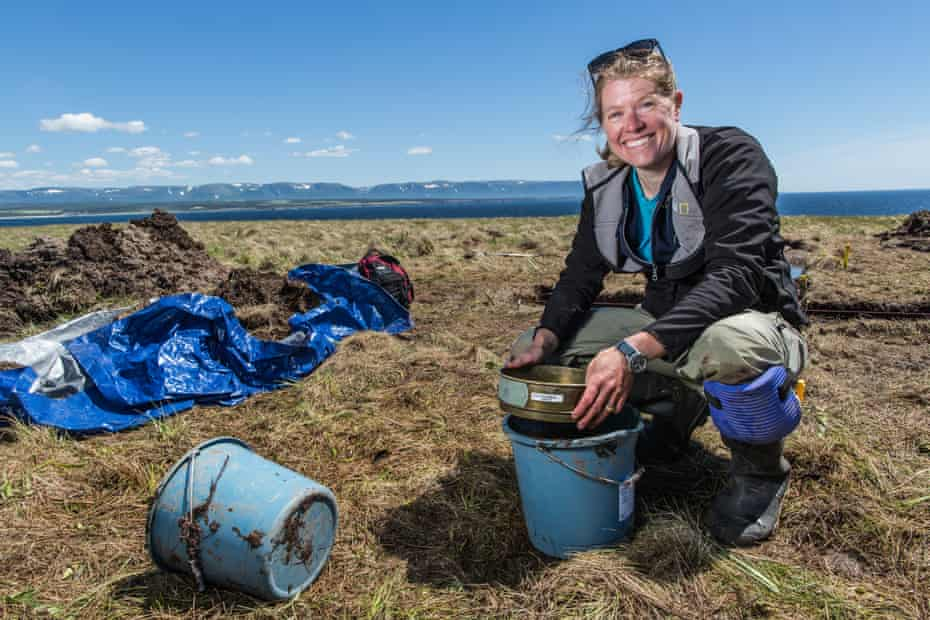 sarah parcak with buckets and a riddle on a sunny day at a dig in newfoundland