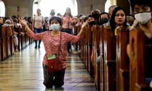 A Filipino Catholic wearing a protective mask amid a coronavirus scare kneels to pray
