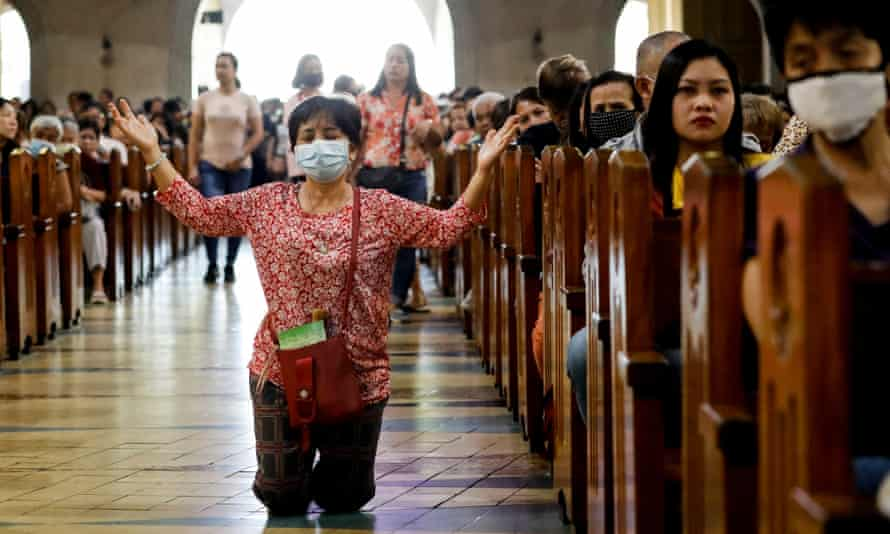 A Filipino Catholic wearing a protective mask amid a coronavirus scare kneels to pray