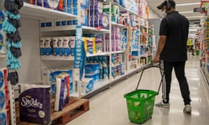 A man walks past the toilet paper in an Asda supermarket in Walthamstow, London as supermarkets urge people not to panic buy.