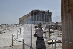 Tourists behind plexiglass take photographs at the entrance of the Acropolis. Greece reopened open-air archaeological sites to the public after a two-month closure.