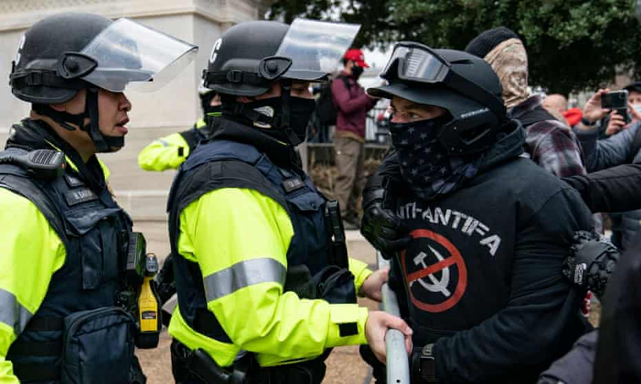 A rioter confronts police officers at the US Capitol on 6 January.