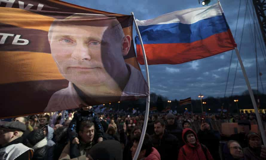 A flag with the portrait of Russian president Vladimir Putin waves over the crowd during the Vesna (Spring) festival in Moscow commemorating the third anniversary of the annexation of Crimea.