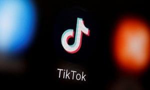 A TikTok logo is displayed on a smartphone