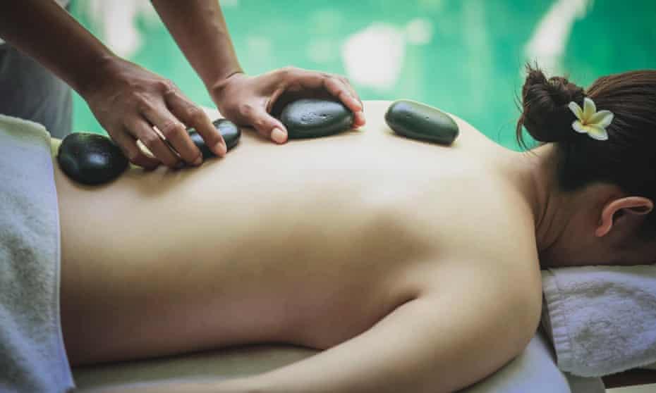 Young woman having hot stone massage.