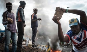 Opposition supporters hold up bricks as they block streets and burn tyres during a protest on Wednesday in Kisumu, where demonstrations are now prohibited.