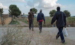 Migrant workers return from the fields in Campobello di Mazara