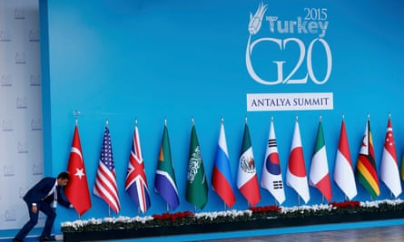An official adjusts a Turkish flag before the G20 summit in Antalya