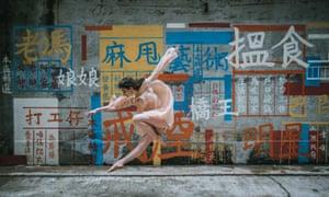A dancer from OTC Graffitt performs in front of street art in Hong Kong.