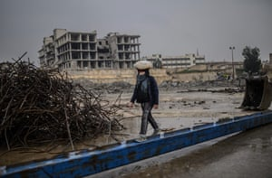 A young man carries a bag of bread on his head as he walks along a beam in the northern Syrian city of Raqa.