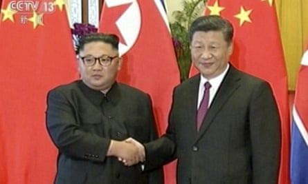 Kim Jong-un and Xi Jinping shake hands in the Great Hall of the People in Beijing.