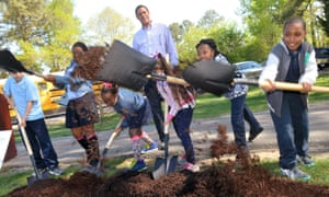 Virginia, US - Students from a primary school in Petersburg shovel soil on to a freshly planted dogwood tree as the mayor, Howard Myers, looks on