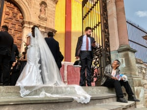 Category: Street Level. Title: A Wedding and the Street Seller. A wedding is about to take place at the Basilica in downtown Guanajuato, Mexico, where I live. In my street photography I like to create images that are at first glance visually interesting, but upon further inspection, reveal a story that may cause the viewer's eyes to linger and mind to wander
