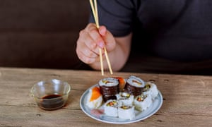 A man eating sushi rolls with chopsticks.