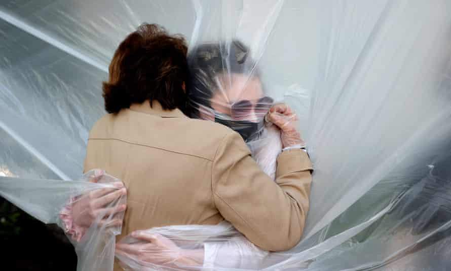 On New York family found an inventive way be together on Memorial Day, hugging each other through a plastic drop cloth.