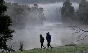 Two early walkers brave the cold at a park east of Melbourne