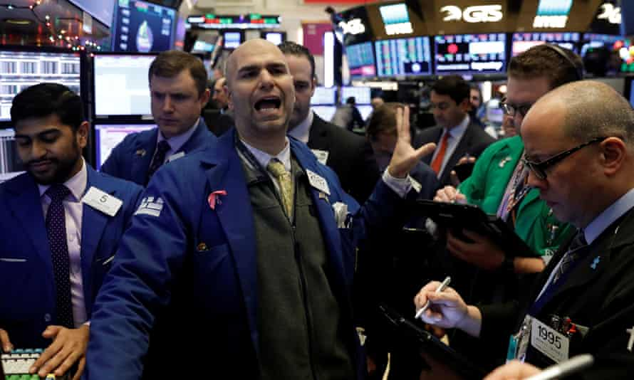 Traders work on the floor of the New York stock exchange as the Dow Jones industrial average rises above 25,000.
