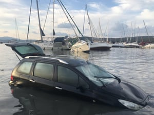 Boats anchored to the coast and a car are seen damaged after a magnitude 6.6 quake shook Turkey's Seferihisar coastline in İzmir