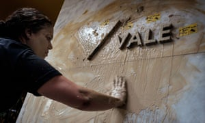 A woman spreads muddy water on the façade of Brazilian mining company Vale headquarters