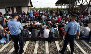 Migrants wait for a train at a railway station, near the official border between Serbia and Croatia, near Eastern-Croatian town of Tovarnik