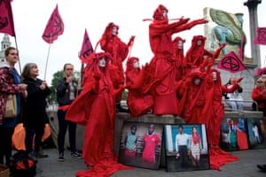 The Invisible Circus - visual artists dressed in red robes - perform the true story of the climate and ecological emergency.