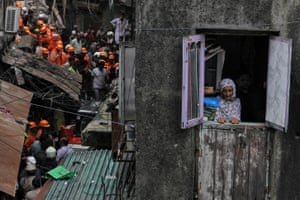Mumbai, IndiaA resident looks out of her house as rescue workers search for survivors at the site of a collapsed building