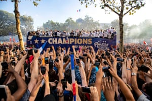 French supporters greet the France's national soccer team players as they stand on the rooftop of a bus during a parade down the Champs-Elysee avenue in Paris,
