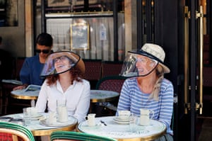 Customers wear protective visors as they have breakfast on the terrace of Cafe de Flore in the Latin Quarter in Paris