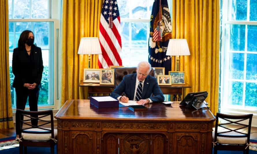 Joe Biden signs the American Rescue Plan as Kamala Harris looks on in the Oval Office on 11 March.