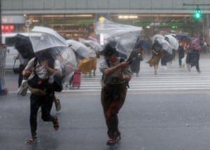 Tokyo, Japan: Pedestrians protect themselves from heavy rainfall caused by Typhoon Jongdari