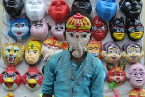 Hyderabad, India An Indian boy wears a mask of Hindu deity Ganesha at a stall outside a temple during the Ganesh Chaturthi festival