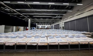 Hundreds of beds for coronavirus patients are lined up to be placed in rooms at a field hospital under construction in the Stockholm International Fairs facility.